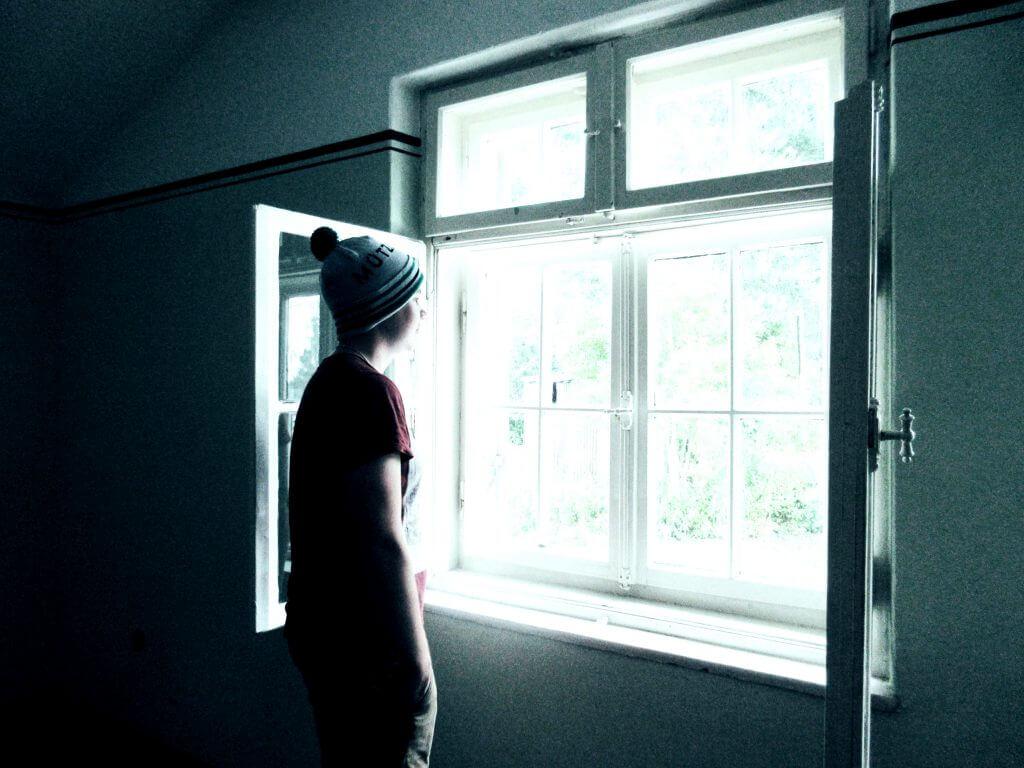 Mann mit Mütze am Fenster