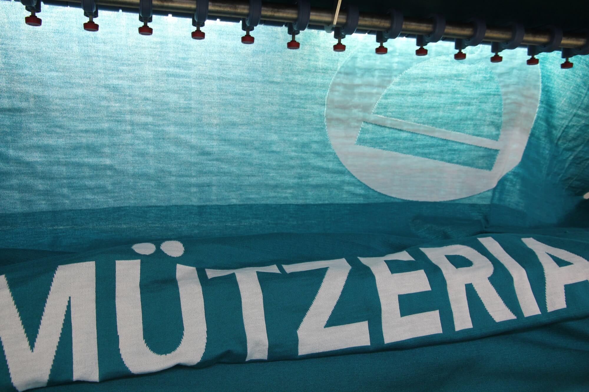 Das MÜTZERIA-Logo in der Strickmaschine