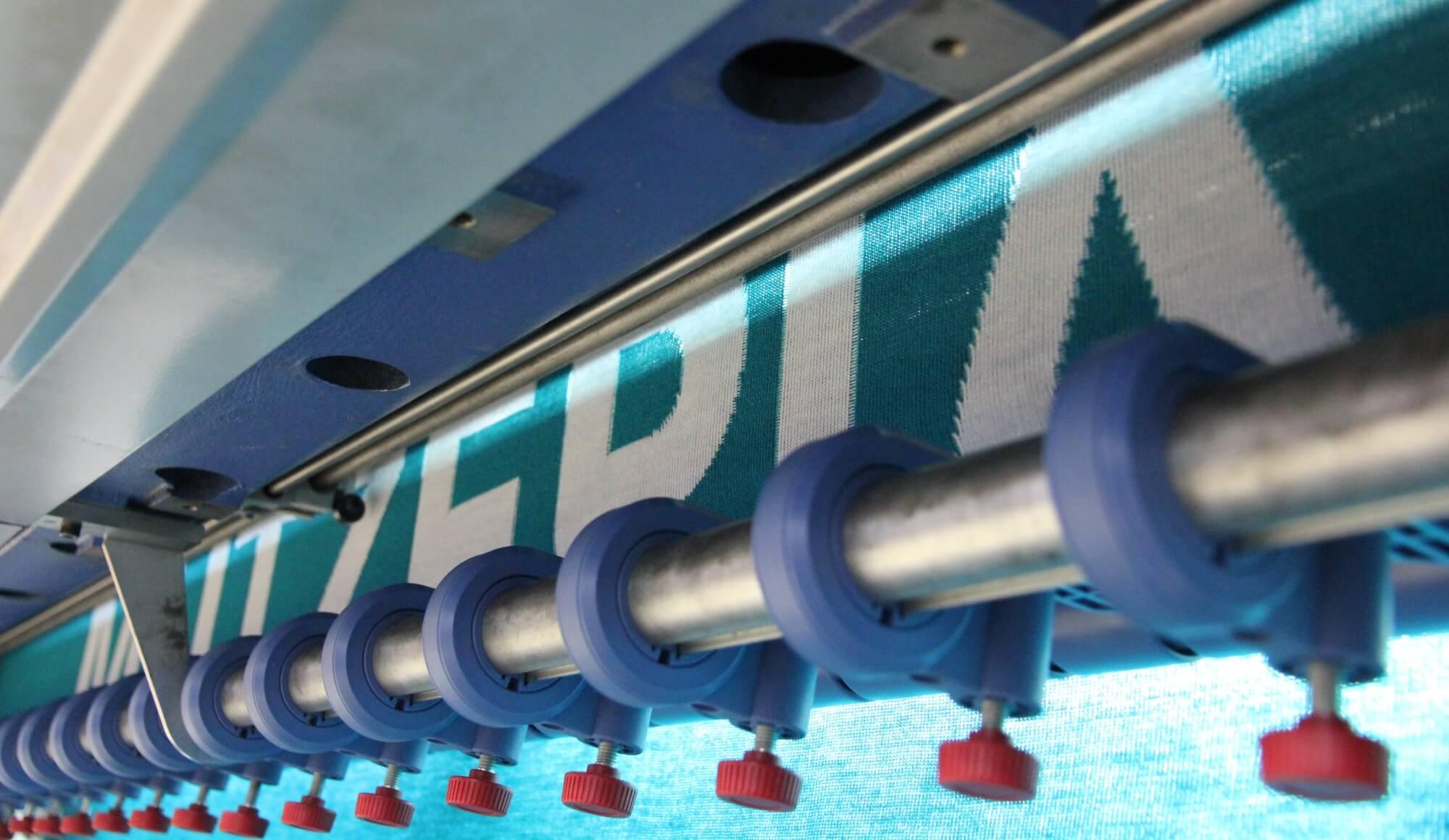 Nahaufnahme des MÜTZERIA-Schriftzugs in der Strickmaschine